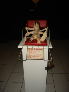 MON ENFANCE: Vintage tortured doll strapped to child's bicycle seat and emergency sign from 1920s elevator, $280